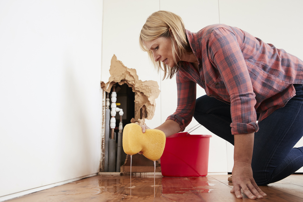 Woman cleaning up water from a burst pipe | Terry's Plumbing Pittsburgh